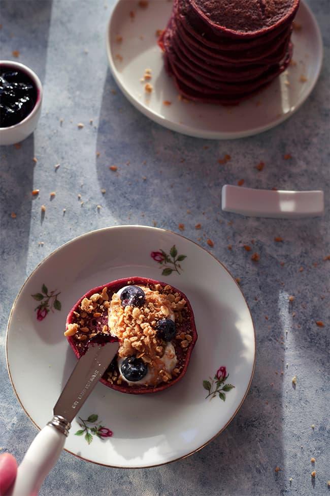 À table : pancake betterave myrtille, yaourt de brebis, myrtilles fraîches et céréales servi dans une assiette